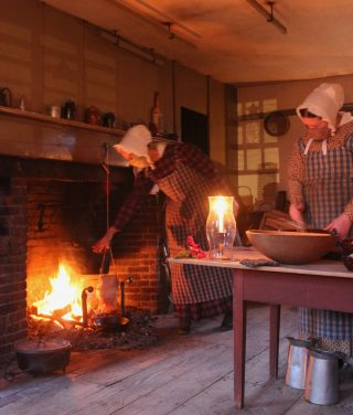 Two costumed interpreters cook in the Freeman Farmhouse