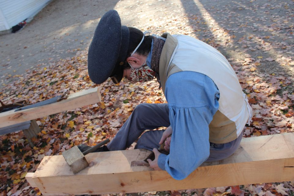A costumed historian cutting a mortise
