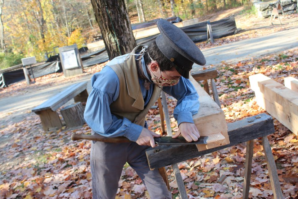 A costumed historian uses a slick on a beam for the frame of the cabinetmaking shop