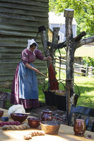 a costumed historian works at the dye pit