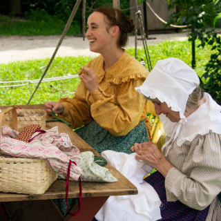 2 women in 1830s dress sewing clothing