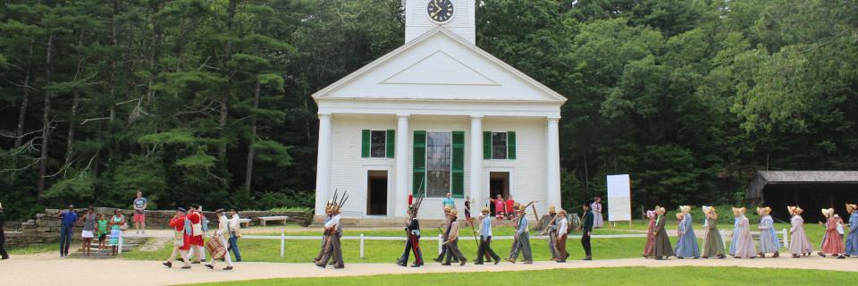 Costumed historians at the Village walk on parade